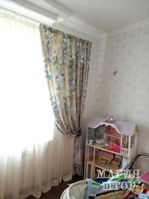 подхваченная штора с современными узорами в детскую
